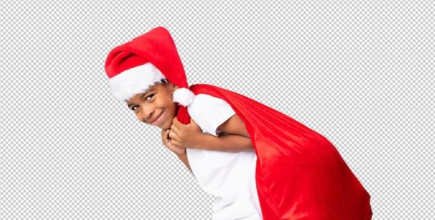 Afroamerikanerjunge mit weihnachtshut und nehmen einer tasche mit geschenken