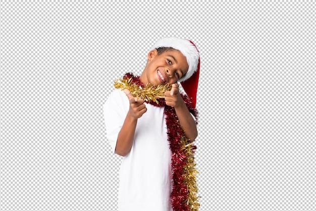 Afroamerikanerjunge mit weihnachtshut zeigt finger auf sie mit einem überzeugten ausdruck