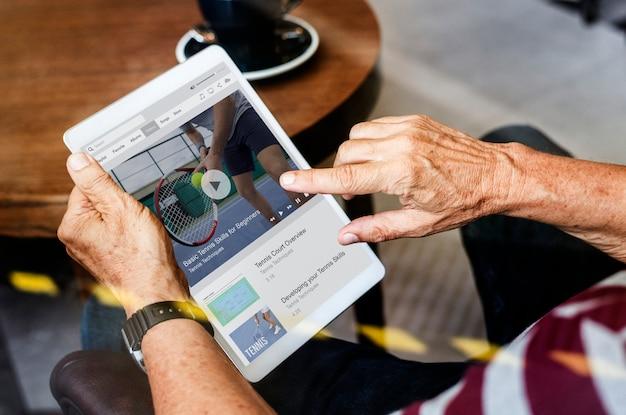Alter mann, der die nachrichten auf einer digitalen tablette aufpasst