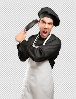 Angry junge chef mit einem kochutensilien