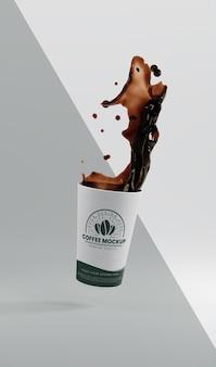 Anordnung der kaffeetasse aus papier mit kaffeespritzer
