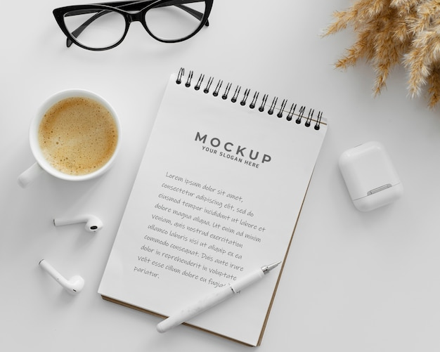 Anordnung mit mock-up-notizblock auf einem schreibtisch