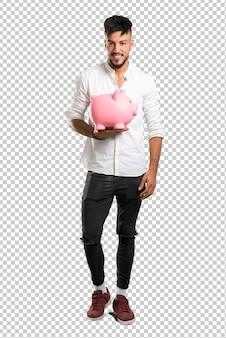 Arabischer junger mann mit dem weißen hemd, das ein großes piggybank hält