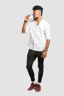 Arabischer junger mann mit dem weißen hemd, das heißen kaffee in der mitnehmpapierschale hält