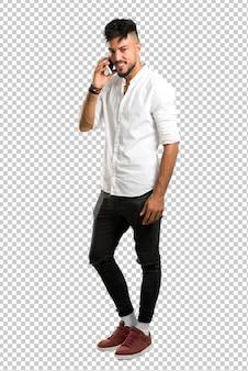 Arabischer junger mann mit weißem hemd, das ein gespräch mit dem handy mit jemandem hält