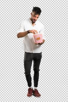 Arabischer junger mann mit weißem hemd popcorn in einer großen schüssel essend