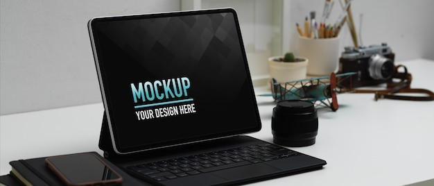 Arbeitsbereich mit digitalem tablet-modell, kaffeetasse und zubehör