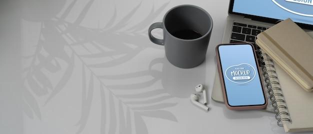 Arbeitsbereich mit modell des smartphones, laptop neben notebooks