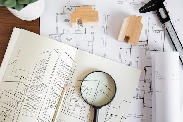Architekturzusammensetzung mit papiermodell und -lupe