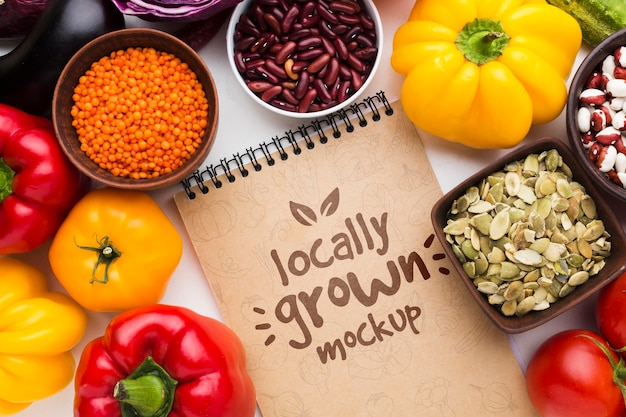 Arrangement von lokal angebautem gemüse-modell und notizblock