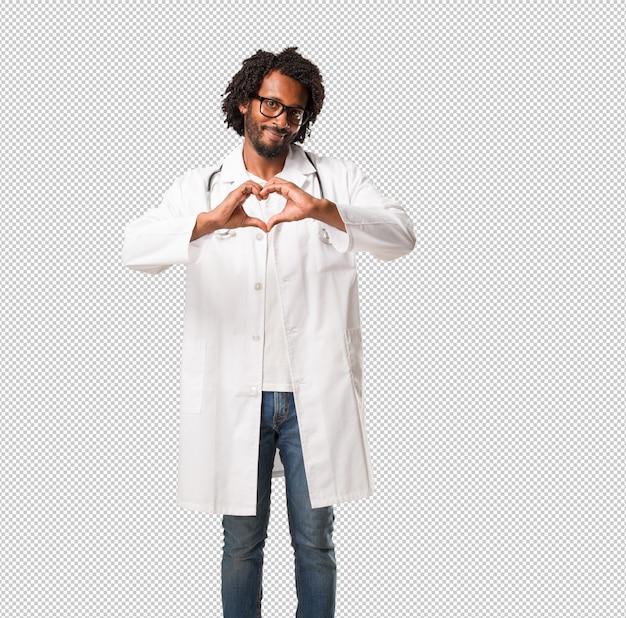 Arzt des hübschen afroamerikaners, der ein herz mit den händen, ausdrückend von der liebe und von der freundschaft, glücklich und lächelnd macht