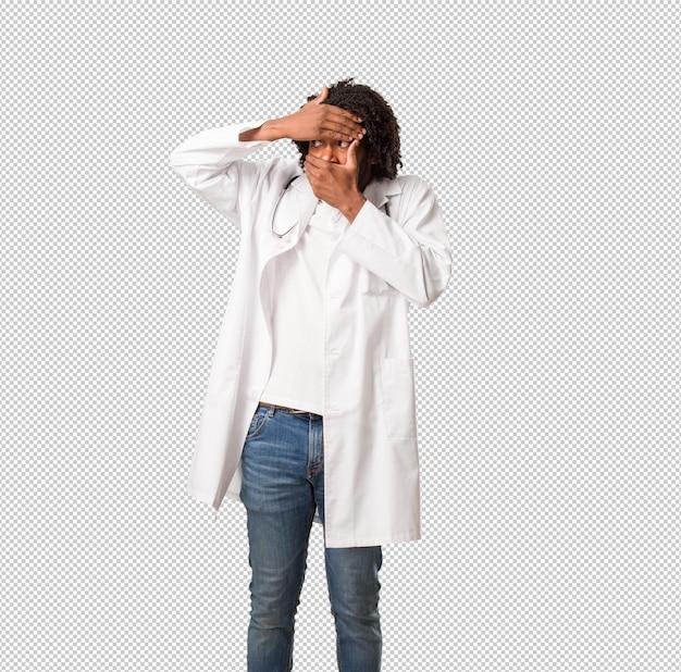 Arzt des hübschen afroamerikaners fühlt sich besorgt und erschrocken und schaut und bedeckt gesicht, konzept von furcht und angst