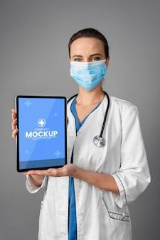 Arzt mit mittlerem schuss, der tablette hält
