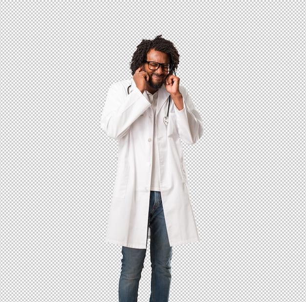 Arztbedeckungsohren des hübschen afroamerikaners mit den händen, verärgert und müde vom hören etwas tones
