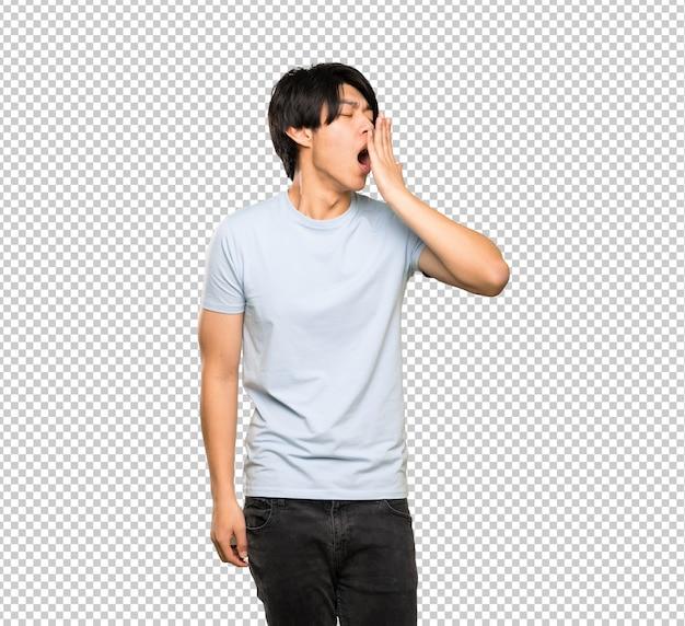 Asiatischer mann mit blauem hemd weit offenen mund mit der hand gähnend und bedeckend