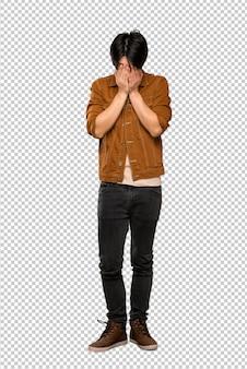 Asiatischer mann mit brauner jacke mit müdem und krankem ausdruck