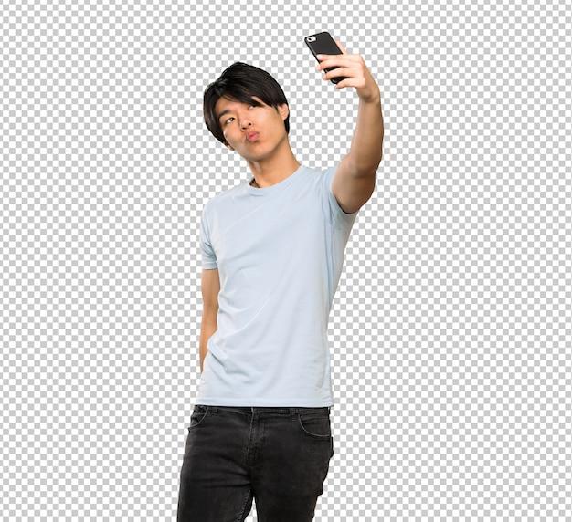 Asiatischer mann mit dem blauen hemd, das ein selfie macht
