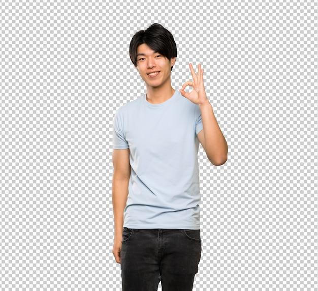 Asiatischer mann mit dem blauen hemd, das okayzeichen mit den fingern zeigt