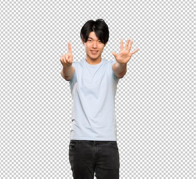 Asiatischer mann mit dem blauen hemd, das sechs mit den fingern zählt