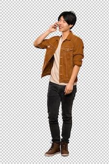 Asiatischer mann mit der braunen jacke, die ein gespräch mit dem handy hält