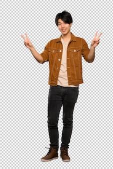 Asiatischer mann mit der braunen jacke, die siegeszeichen mit beiden händen zeigt