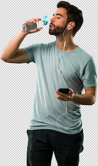 Athletisches trinkwasser des jungen mannes und hören musik
