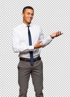 Ausdehnungshände des jungen afroamerikanischen geschäftsmannes zur seite, damit die einladung kommt
