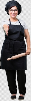 Bäckerfrau des vollen körpers von mittlerem alter, die heraus erreicht, um jemand zu grüßen oder zu gestikulieren, um zu helfen, glücklich und aufgeregt