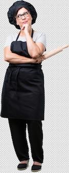 Bäckerfrau des vollen körpers von mittlerem alter, die zweifelt und verwirrt, an eine idee denkt oder über etwas sich sorgt