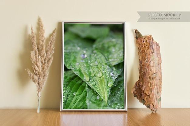 Bearbeitbare psd-modellvorlage mit silbernem a4-rahmen, flauschiger feldpflanze und holzstück