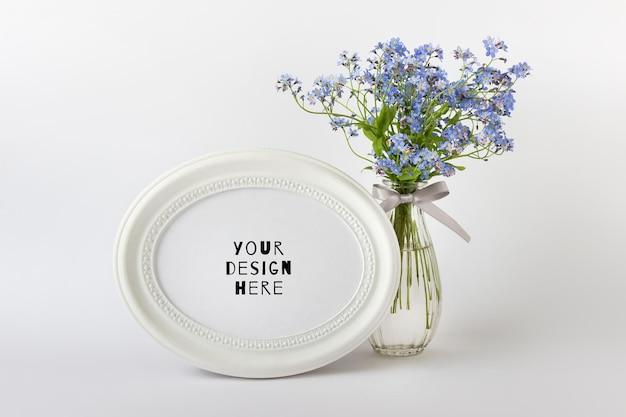 Bearbeitbare psd-modellvorlage mit weißem ovalem rundem rahmen und blauen sommerblumen auf weißem hintergrund