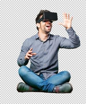 Bemannen sie das sitzen auf dem fußboden, der gläser einer virtuellen realität trägt