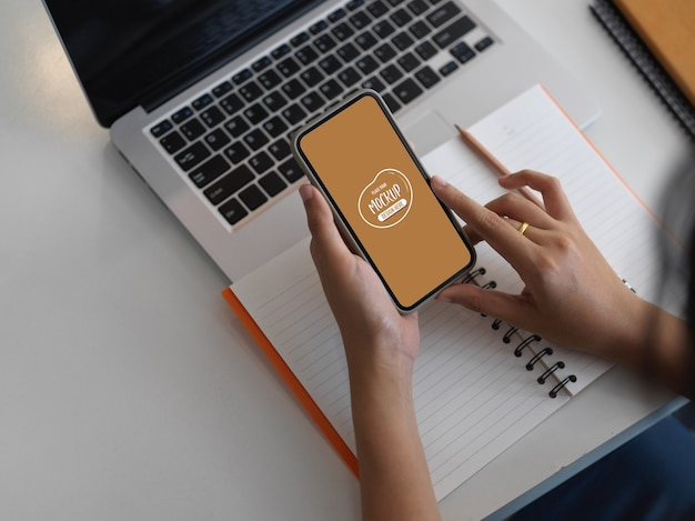 Beschnittene aufnahme der geschäftsfrau mit mock-up-smartphone in ihrem arbeitsbereich