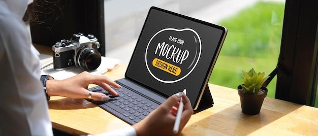 Beschnittene aufnahme der journalistin, die mit digitalem tablett und kamera auf bar in der cafeteria arbeitet