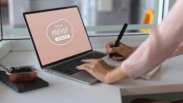 Beschnittene aufnahme der jungen frau, die an ihrem projekt mit modell-laptop-computer im büroraum arbeitet