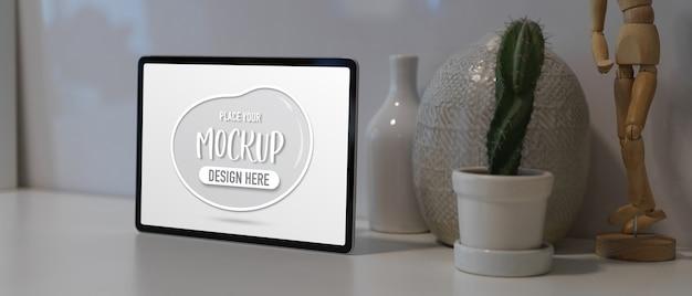 Beschnittene aufnahme des arbeitsbereichs mit mock-up-tablette, kaktustopf und dekorationen auf weißem tisch