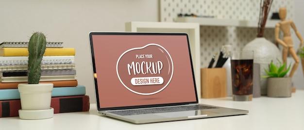 Beschnittene aufnahme des arbeitsplatzes mit modell laptop, bücher, briefpapier und dekorationen auf weißem tisch