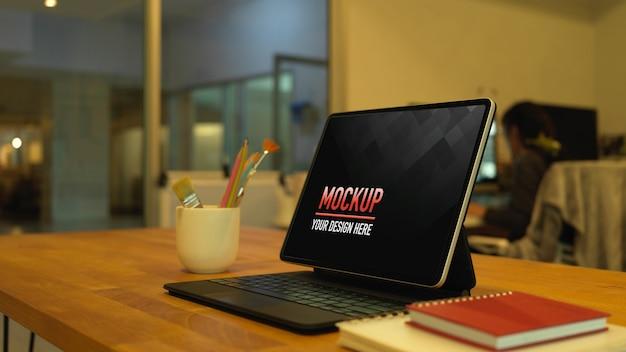 Beschnittene aufnahme des arbeitstisches mit digitalem tablet, pinseln und notizbüchern