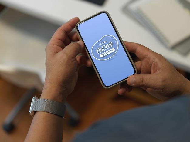 Beschnittene aufnahme eines mannes, der ein nachgebildetes smartphone verwendet, während er am arbeitstisch im büroraum steht