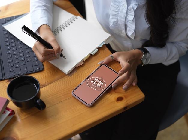 Beschnittene aufnahme von weiblichen suchinformationen auf modell-smartphone und schreiben sie es in notizbuch