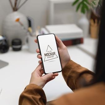 Beschnittener schuss der freiberuflerin unter verwendung des modell-smartphones