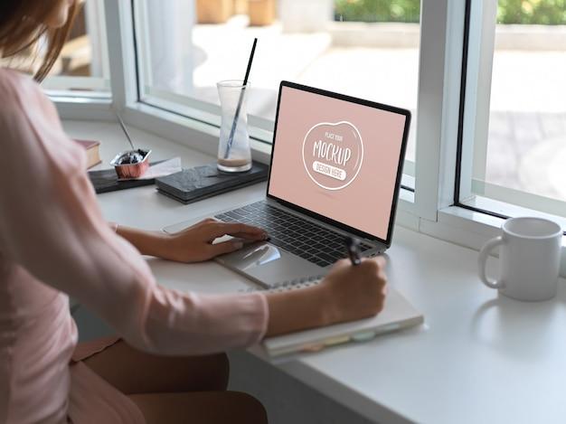 Beschnittener schuss der jungen arbeiterin, die auf modell-laptop-computer tippt