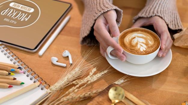 Beschnittener schuss der jungen frau, die latte-kunstkaffee auf holztisch mit schreibwaren hält