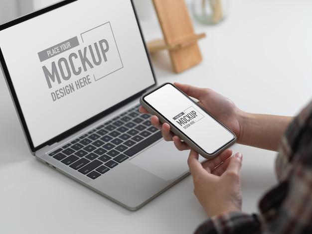 Beschnittener schuss der jungen frau, die schein-smartphone hält, während schein-laptop-computer verwendet wird