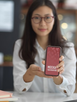 Beschnittener schuss der jungen geschäftsfrau, die smartphone des leeren bildschirms im büroraum zeigt, beschneidungspfad