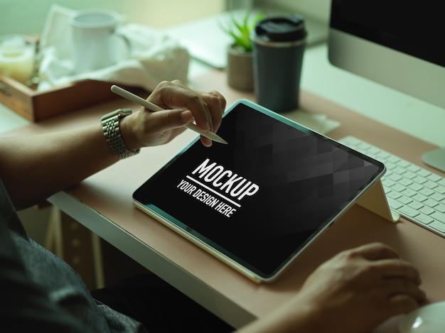 Beschnittener schuss der männlichen hände unter verwendung des digitalen tablets des modells auf computertisch im büroraum