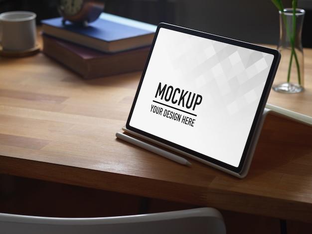 Beschnittener schuss des arbeitsbereichs mit digitalem tablett, büchern und kopierraum auf holztisch