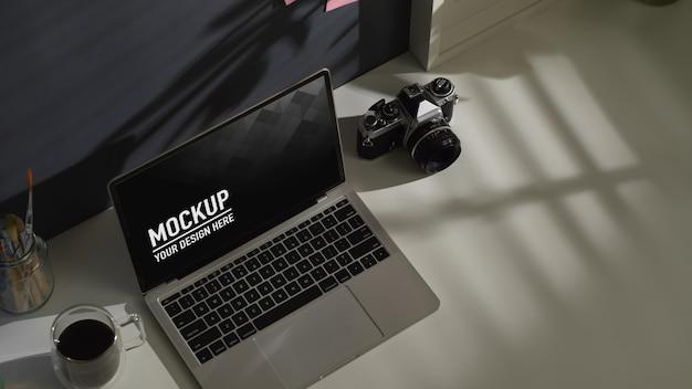 Beschnittener schuss des arbeitstisches mit laptop-modell