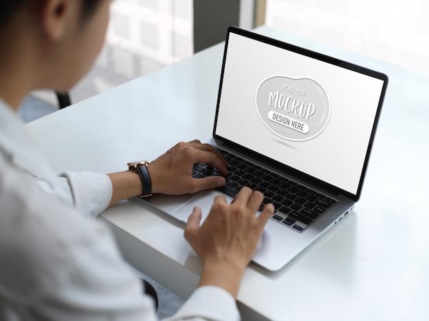 Beschnittener schuss des jungen geschäftsmannes, der auf modell-laptop-computer im modernen büroraum tippt