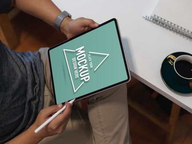 Beschnittener schuss des männlichen büroangestellten, der mit dem digitalen tablett des modells arbeitet